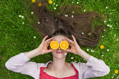 Summer oranges. Lady with oranges laying on grass Royalty Free Stock Images