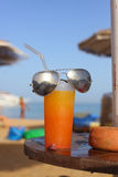 Summer oranhe shake coctail with straw and sun glasses on the se Stock Photo