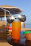 Summer oranhe shake coctail with straw and sun glasses on the se Stock Photos