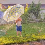 Summer outdoor activities. Children playing outdoor on front yard. Boy with umbrella having fun near automatic plant royalty free stock image