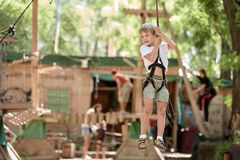 Summer outdoor activity. Happy boy enjoying summer activity in the rope park stock image