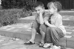 Summer outdoor girl comforting a sad boy. Black and white photo. Stock Photos