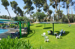 The summer outdoor pool in a room with green lawn grass, trees and umbrellas to relax, the Negev, Israel, 2015 Stock Photography
