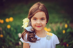 Summer outdoor portrait of adorable smiling kid girl. With yellow flowers on background Stock Photo