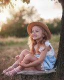Summer outdoor portrait of beautiful happy child. Little girl wear a hat. Your kid sits at the park or forest outdoors, spring stock photo