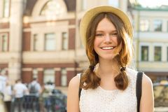 Summer outdoor portrait of smiling beautiful teenager girl 13, 14 years old wearing hat on city street, copy space royalty free stock images