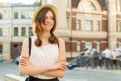 Summer outdoor portrait of smiling beautiful teenager girl 13, 14 years old wearing hat on city street, copy space royalty free stock photo