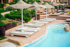 Summer outdoor swimming pool and sun loungers Royalty Free Stock Photography