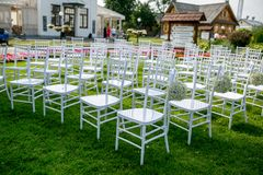 Summer outdoor wedding ceremony decoration. White classic chairs to accommodate guests at the ceremony. Ball gypsophila decoration stock photo