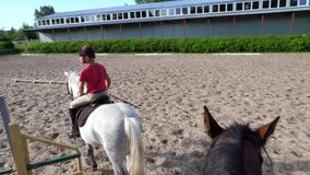 Summer, outdoors, boy rider, jockey riding on thoroughbred beautiful white stallion, horse, on the training sand field. Ground. boy learns to ride a horse in stock footage