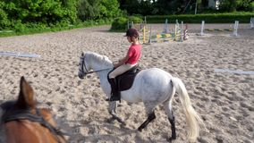 Summer, outdoors, boy rider, jockey riding on thoroughbred beautiful white stallion, horse, on the training sand field. Ground. boy learns to ride a horse in stock video footage