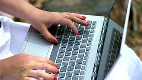 Summer, outdoors. close-up of female hands with bright red manicure, type on the laptop keyboard. working on laptop. Summer, outdoors. close-up of female hands stock footage