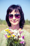 Summer outdoors vintage portrait of woman with bunch of field fl Stock Photo