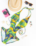 Summer outfit, beach outfit, summer stuff. Exotic pattern swimsuit, retro sunglasses, pink retro camera and straw hat. Flat lay, t. Op view Stock Images