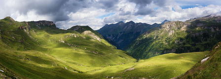 Summer panorama of Austrian Alps. With green hills, grass and clouds. View from Grossglockner High Alpine Road Royalty Free Stock Images