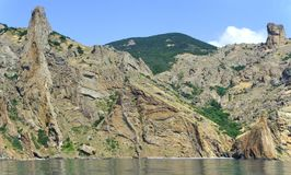 Summer panorama of the Crimean mountains Karadag from the sea. Fabulous summer sea voyage along the protected shores of the Crimean mountains Karadag Royalty Free Stock Images