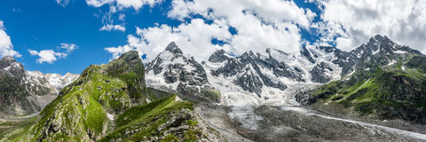 Summer panorama view of the Caucasian snow coverd peaks. And the glacier at the foot of it. Russia, Kabardino-Balkaria, Elbrus region Royalty Free Stock Photography