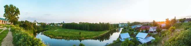 Summer panorama of the village by the river Royalty Free Stock Photos