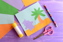 Summer paper card, scissors, glue stick, colored paper sheets on lilac wooden background. Hippo and palm tree preschool craft Royalty Free Stock Photography
