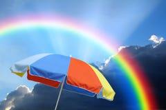 Summer parasol brolly umbrella under rainbow storm sky stock photo