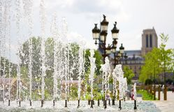 Summer in Paris. View of Notre-Dame de Paris through the fountain. Focus on the water jets Royalty Free Stock Photo