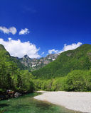 Summer in the park. Beautiful image of creek with gravel beach, forest and mountains with blue sky. taken in Golden Ears Provincial Park, British Columbia royalty free stock photography