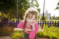 In the summer in the park a little funny girl is riding on a swing. stock photography