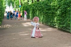 In the summer park Little girl in 1800`s dress with fan. SAINT PETERSBURG, RUSSIA - AUGUST 18, 2017: Little girl in 1800`s dress with fan for a walk in Summer Royalty Free Stock Images