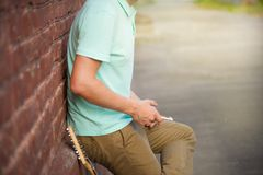 Summer, party, young stylish guy standing near brown brick wall, hands holding mobile phone next to guitar, sunlight royalty free stock image