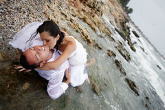 Summer passion (lovers portrait). Beautiful passionate couple expressing their passion for each other by the sea shore royalty free stock images