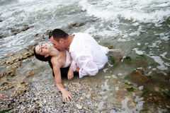 Summer passion (lovers portrait). Beautiful passionate couple expressing their passion for each other by the sea shore stock photography