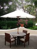 Summer patio with tables and wooden chairs under umbrella Stock Image