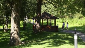 Summer pavilion in park. People strolling through the park past a wooden summer house on a shiny sunny day stock video