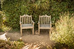 Summer peaceful vintage garden nook with metal furniture. Summer peaceful vintage garden nook with two vintage wooden chairs. Outdoor relaxation scenery Stock Photography