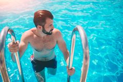 Summer photo of muscular smiling man in swimming pool. Happy male model in water on summer vacations Royalty Free Stock Image