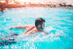 Summer photo of muscular smiling man in swimming pool. Happy male model in water on summer vacations Stock Photo