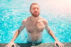 Summer photo of muscular smiling man in swimming pool. Happy male model in water on summer vacations Stock Photography