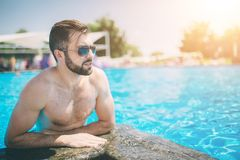 Summer photo of muscular smiling man in swimming pool. Happy male model in water on summer vacations. Summer photo of muscular smiling man in swimming pool Royalty Free Stock Photography