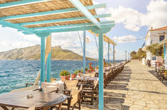 Summer photo with panoramic view from Aegina island in Greece. Beautiful place for making lunch on seafront with wooden roof. Stock Photography