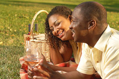 Summer picnic. Young couple enjoying a beautiful summer day outside with a wine picnic Stock Images