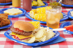 Summer picnic feast. A cheeseburger with potato chips and corn on the cob on a picnic table loaded with food Stock Photo