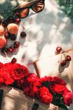 Summer picnic in the garden with red garden roses in a wicker bag, sunglasses and cherry berries on a blanket.