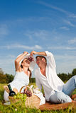 Summer picnic - Happy couple in meadow eat grapes Stock Image