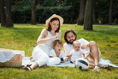 Summer picnic. Happy parents with two kids dressed in white casual clothes are sitting on the coverlet on green grass. stock photography
