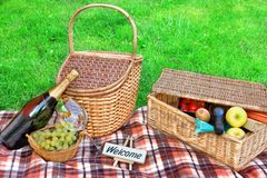 Summer Picnic on the Lawn. Picnic blanket, basket with food and wine, champagne, grape and sign WELCOME Stock Image