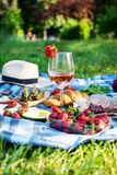 Summer picnic in the park on the grass. Wine, fruit and croissants.  royalty free stock photo