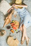 Summer picnic setting with wine in womans hands, baguette, fruits Royalty Free Stock Image