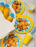 Summer picnic. Sweet picnic - orange juice and muffins, croissants and cakes on yellow and blue disposable dishes. Top view stock photos