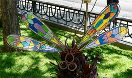 Stained Glass Dragon Fly. This is a Summer picture of a public art exhibit of a stained glass Dragon   in the sidewalk gardens along Michigan Avenue located in royalty free stock images