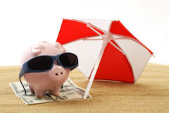 Summer piggy bank standing on towel from greenback hundred dollars with sunglasses on the beach sand under red and white sunshade. Horizontal Stock Images